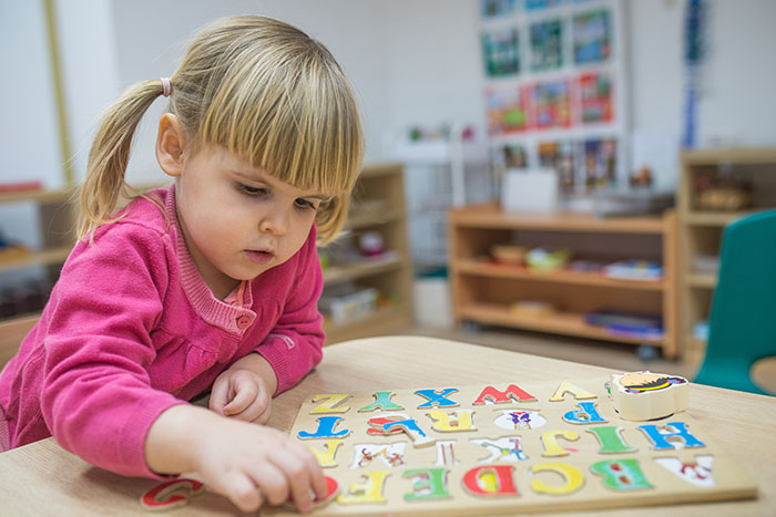 Little girl playing with wooden puzzle at a Preschool & Daycare Serving Brighton, MI