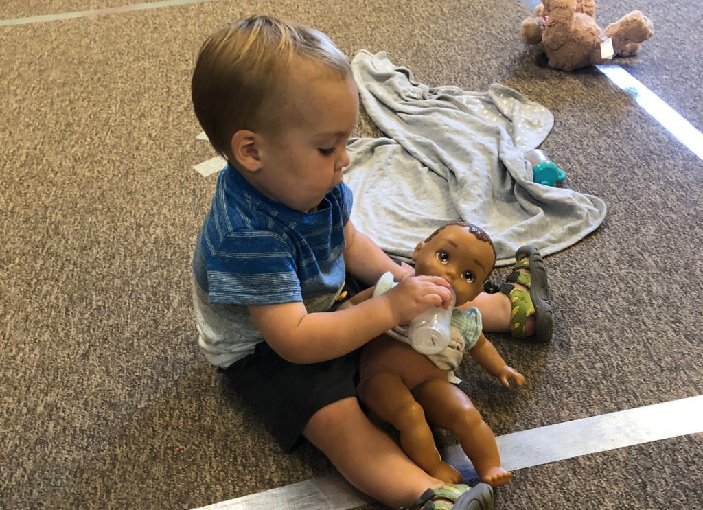infant playing with doll at a Preschool & Daycare Serving Brighton, MI
