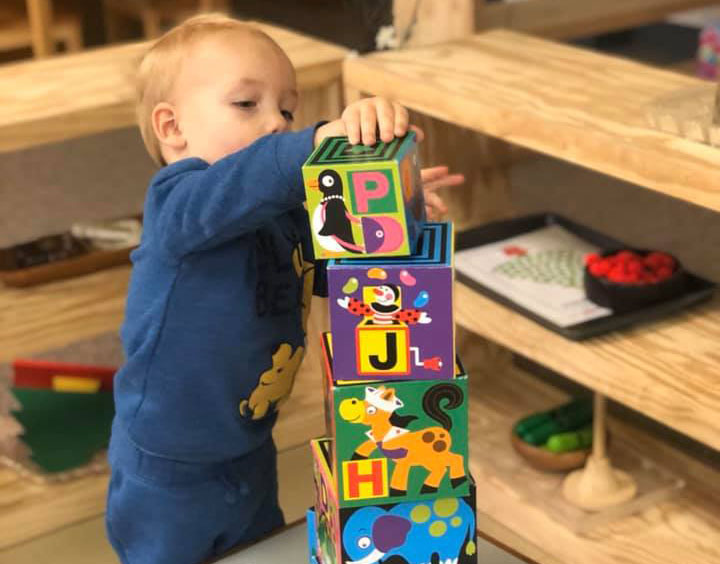 toddler playing with wood blocks at a Preschool & Daycare Serving Brighton, MI