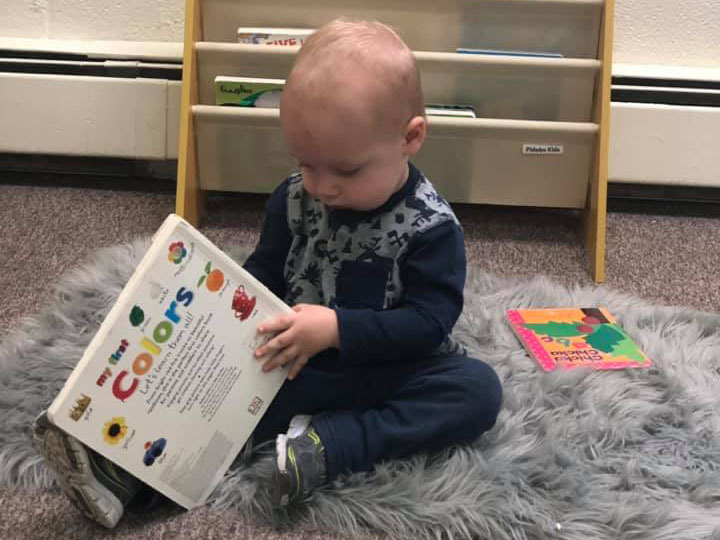 toddler with a book at a Preschool & Daycare Serving Brighton, MI