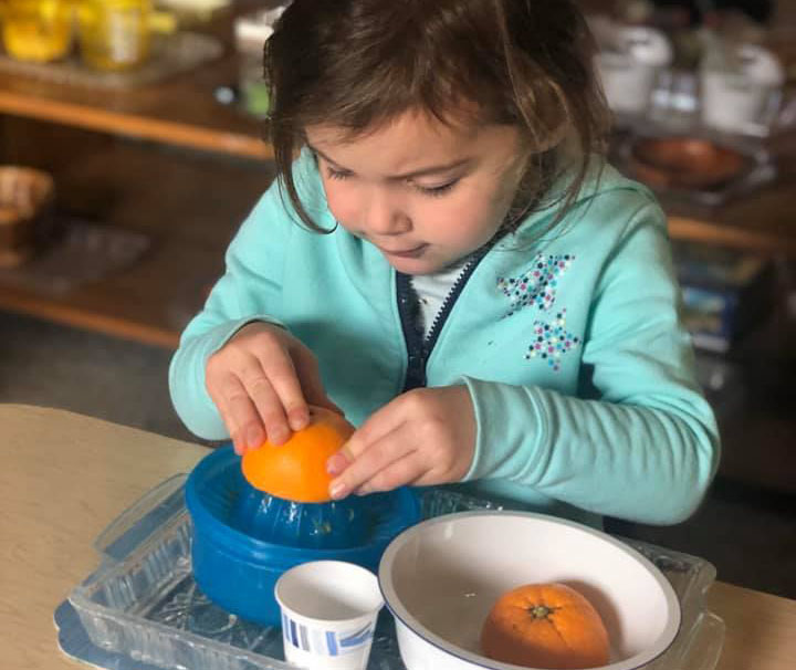 young girl juicing an orange at a Preschool & Daycare Serving Brighton, MI